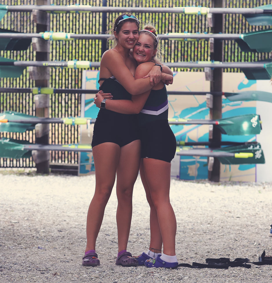 Two female rowers hugging in the boat yard. Oars in horizontal racks in the background