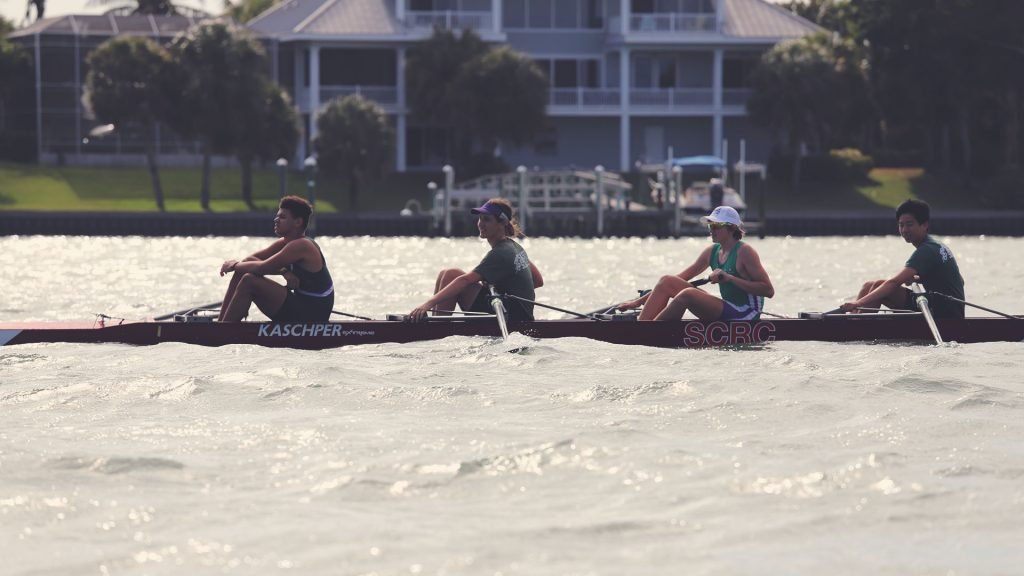 "Men's four. ""Kaschper"" and ""SCRC"" can be read on the bow. Large home in the background."