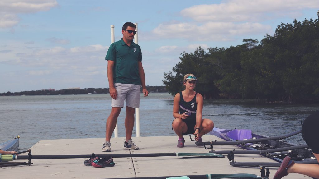 Picture of the dock with coach standing and two female rowers seen squatting preparing a quad.