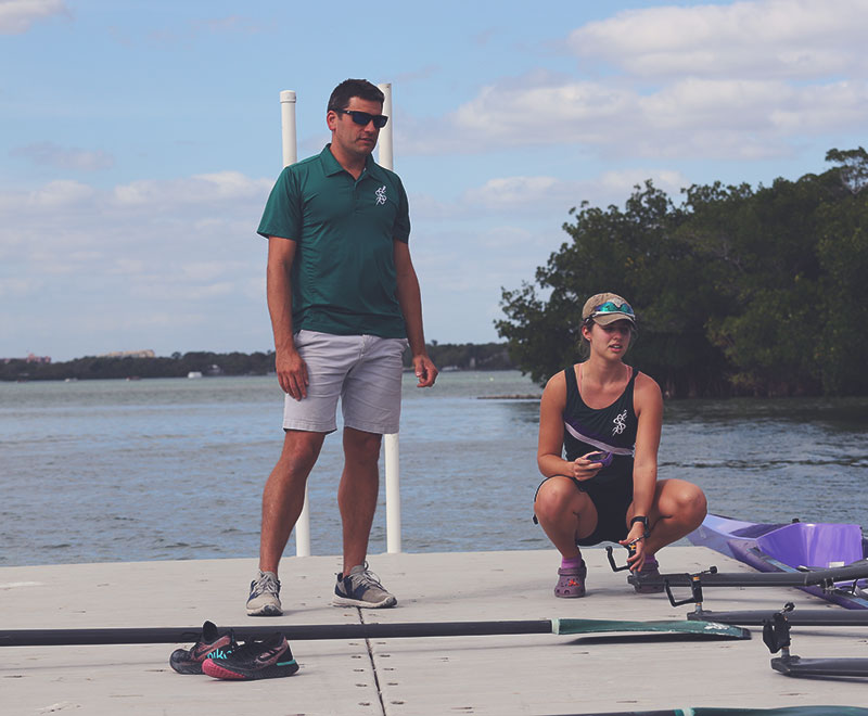 Coach standing on dock with a rower preparing an oarlock for rowing.