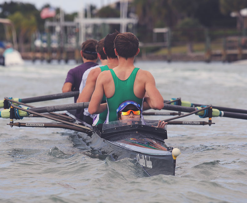 Men's bow coxed for pictured from the bow. Coxswain seen wearing sunglasses. Men's backs seen as they are mid-stroke.