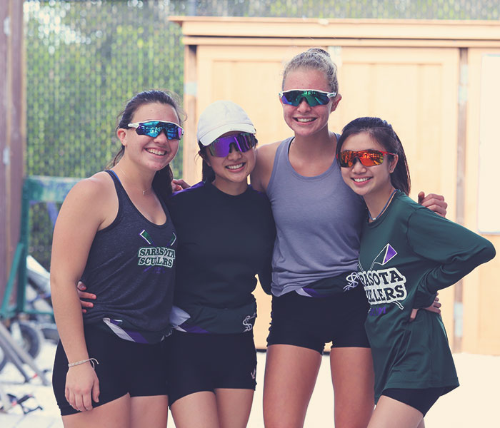 Four smiling women rowers togeter with arms over shoulders and wearing sunglasses in the boatyard