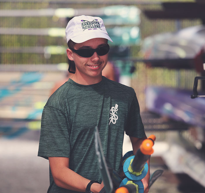 Male rower with Sarasota Scullers hat, sunglasses, and a smile carrying oars.